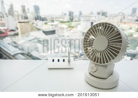 white portable USB desktop fan with USB hub on office table