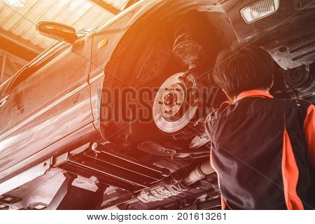 Car Lifted In Automobile Service For Fixing. Garage Automobile Service, Worker Repairs Detail