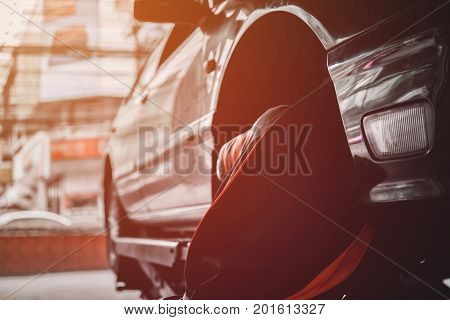 Professional Car Mechanic Changing Wheel In Auto Repair Service. Mechanic Adjusting The Tire At The