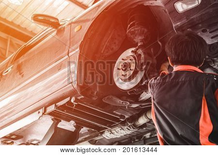 Car Lifted In Automobile Service For Fixing. Professional  Mechanic Male In Garage Automobile Checki