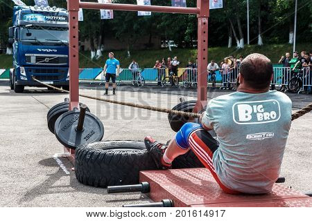 Almaty , Kazakhstan - May 28, 2017. strong man pulling  heavy truck with a rope. City fesitwal sport on the street for a healthy lifestyle. Sports contests for arm-wrestling, heavy lifting, tug-of-war, army bench press