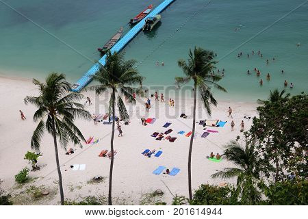Coconut beach with tourists doing activities in high season Ang Thong Island Thailand.