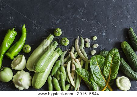Organic green garden vegetables food background. Zucchini peppers beans squashes cucumbers chard on dark background top view. Flat lay