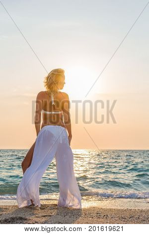 Classy woman on the beach in Greece at sunset