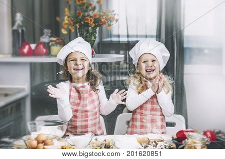 Two Happy Little Girls Child Cook With Flour And Dough At The Table In The Kitchen Is Lovely And Bea