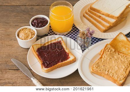 Toast bread with homemade strawberry jam and peanut butter served with orange juice. Homemade toast bread with jam and peanut butter on wood table for breakfast. Delicious toast bread ready to served.