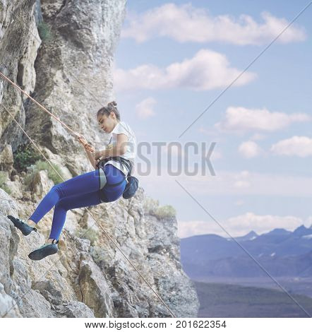 young cheerful woman climbs on the cliff. rock climber Learns to climb rocks on a rocky wall. woman makes hard move and looking up