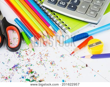 Colorful pencils with colorful pencil shavings and office accessories on white background. Back to school concept.