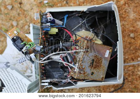 The wiring and motherboard are exposed on an old desktop PC monitor and computer that has been broken and smashed open.