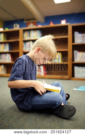 A little second grade elementary school aged boy child is sitting on the carpet reading a book at the school library.
