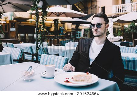 This buisnessman is sitting at the table in restaurant during his lunch time. He hasn't been started to eat his lunch because guy is waiting for colleague. Close up