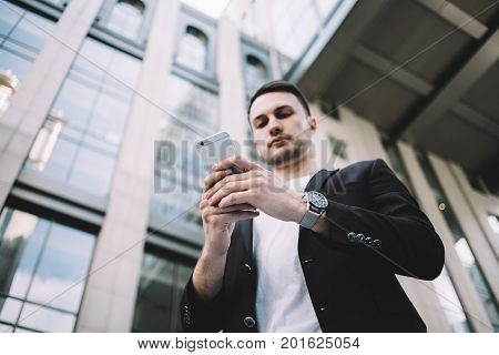 The portrait of a young businessman that is made from the bottom angle. He is standing outside on the street and holding the phone in his arms. Probably he is looking for some information. Close up. Cut view