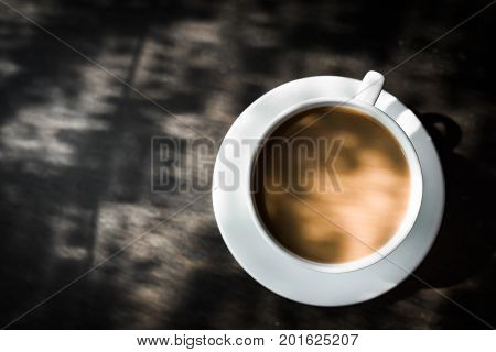 Capuccino mocha latteamericano espresso hot coffee aroma in cup breakfast morning drink on wooden table vintage bar windows in cafe shop with newspaper restaurant backgroundcopy space the left.