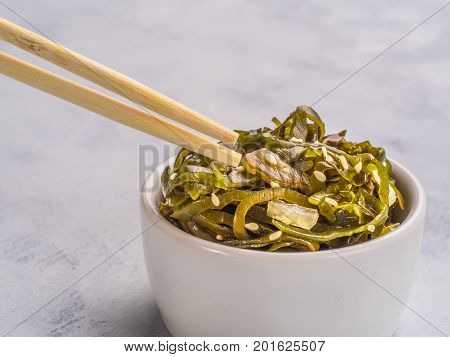 Close up view of kelp seaweed salad with sesame seeds on gray concrete background. Copy space.
