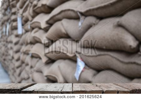 old hemp sacks containing coffee bean in warehouse. stacked sacks in storehouse with wood table for display your product.