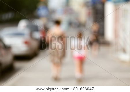 Urred Background. Blurred People Walking Through A City Street