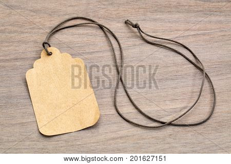 blank paper price tag with a long twine against grained wood