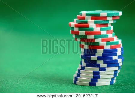 Casino poker chips  on green table background with copy space for your text