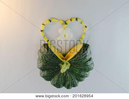 Sliced raw yellow pumpkin heart symbo on white background.