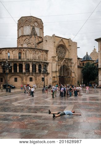 Valencia Spain - June 3 2016: Young man lies on square of Saint Mary with local and tourists in Valencia Old Town in the evening Spain