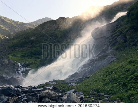 Mountain waterfall in Alps. Scenic Alpine rocky alpine mountines of Sportgastein in summer. Picturesque mountain cascade, great mountain massif, sunny weather. Sport hiking landscape background.