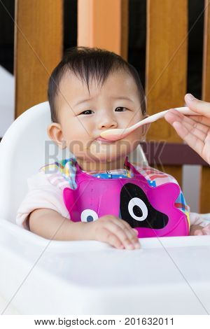 Asian cute baby eating food Mother feeding solid food for young kid eight month at home.