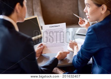 Back view of female business partners discussing terms of agreement before signing contract, interior of cozy boardroom on background
