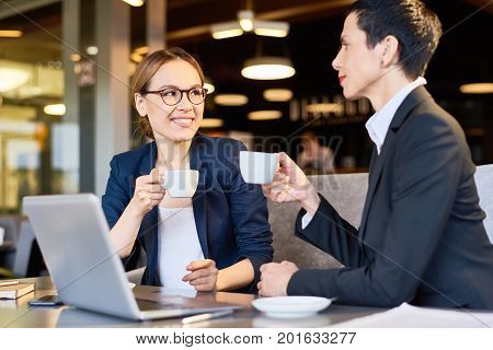 Cheerful coworkers in formalwear chatting animatedly with each other while enjoying fragrant coffee at cozy cafe