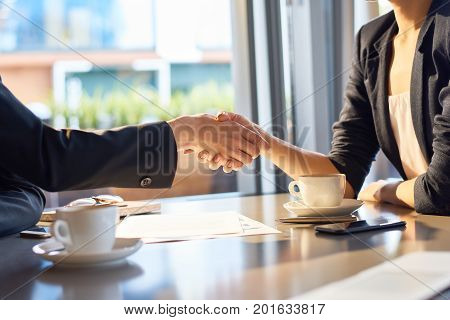 Close-up shot of unrecognizable business partners shaking hands while having negotiations at coffeehouse with panoramic window