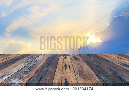 Empty wooden table or plank with sun light sunbeams or sunrays from clouds background for product display.