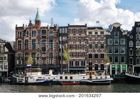 Amsterdam Netherlands - 27 April 2017: Houseboats and living barges in Binnenamstel canal against typical dutch houses with flag of Netherlands and LGBT flag on the facade of buildings Holland Netherlands.