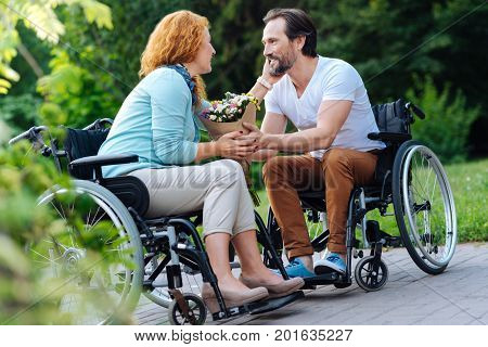 Preserve your love. Nice senior wheelchaired couple expressing love and looking at each other while resting in the park