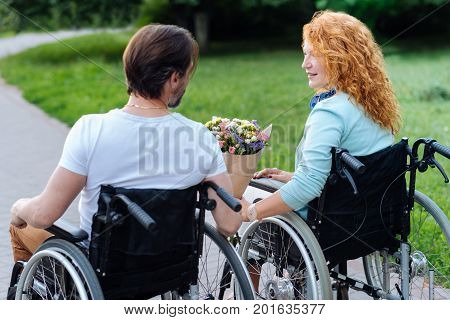 PLeasant day. Nice senior disabled couple sitting in the wheelchairs and walking in the park while a man presenting a bunch of flowers to his nice wife