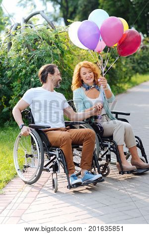 Brighten your day. Cheerful senior disabled couple sitting in the wheelchairs and holding balloons while enjoying free time outdoors