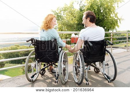Nice rest. Positive delighted senior couple sitting in the wheelchairs and having a celebration while enjoying time outdoors