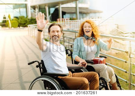 Hey everyone. Cheerful senior wheelchaired man welcoming you while holding a hand of his loving wife while having a wlak in the city