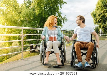 More positivity in life. Overjoyed emotional senior couple sitting in the wheelchairs and expressing joy while having a walk in the park