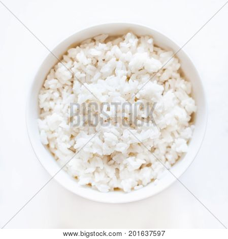 White cooked rice in a white bowl over white background close up