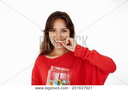 Horizontal isolated picture of charming mixed race teenage girl with brown hair relaxing at home holding big glass jar with candies looking at camera chewing jelly beans gummy bears or marmalades