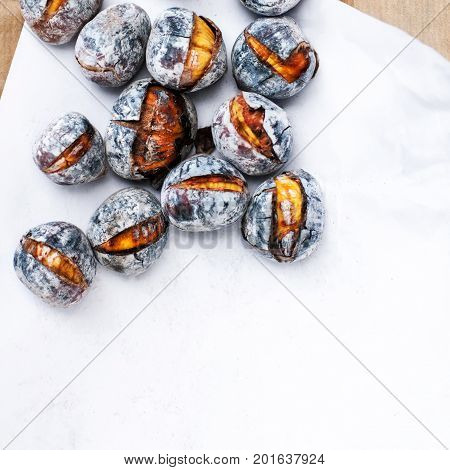 Roasted chestnuts with copy space. Delicious grilled chestnuts over white background
