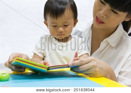 Asian adorable baby one year is looking book for kid support interested with mother parent. Activities family to enhance learning educational.
