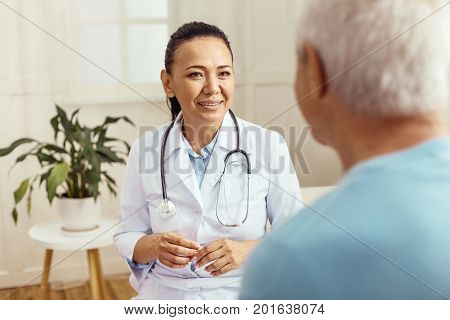 My duties. Cheerful skillful professional doctor looking at her patient and asking him about his health while doing her job