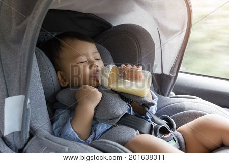 Asian cute baby sleepy drinking milk bottle in modern car seat. Child one year traveling safety on the road. Safe way to travel fastened seat belts in a vehicle with young kid. Trip with an infant.