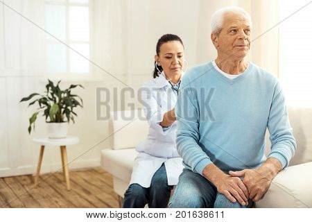 Medical treatment. Smart professional serious nurse sitting behind her patient and wearing a stethoscope while auscultating him
