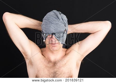 attractive candid european middle-aged male wearing glasses over headscarf making him blind - studio shot on black background