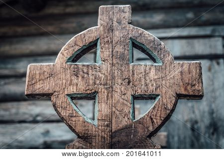 Old gothic style and roughly carved wooden bench with a cross symbol as gable