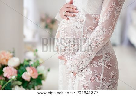 Pregnant woman belly, beautiful lingerie and nightgown. Blured bouquet in background