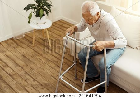 I can do it. Confident pleasant aged man holding a walking frame and standing up from the sofa while trying to walk