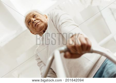 Mobility issues. Thoughtful sad senior man leaning on the walking frame and taking steps forward while walking