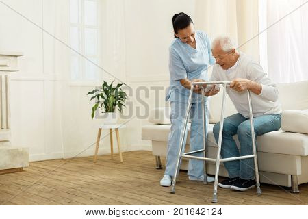 Do not hurry. Delighted positive cheerful caregiver smiling and helping her patient to stand up while being near him